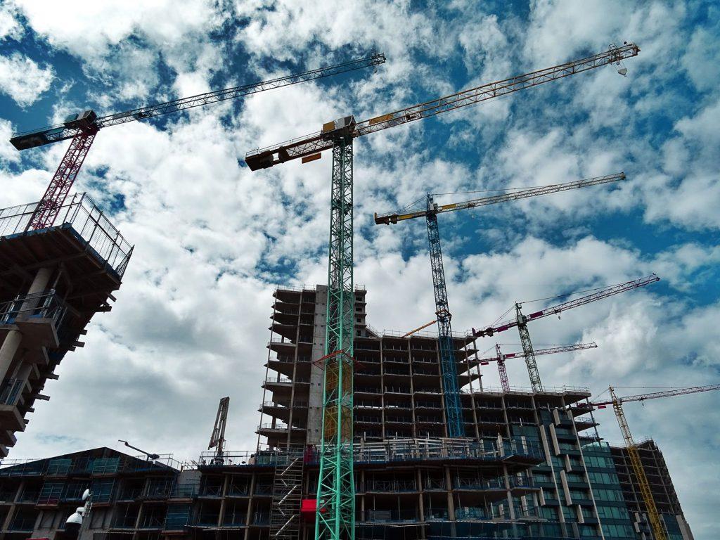 Drie hijskranen op rij voor en achter een gebouw dat onder constructie is en in de steigers staat.