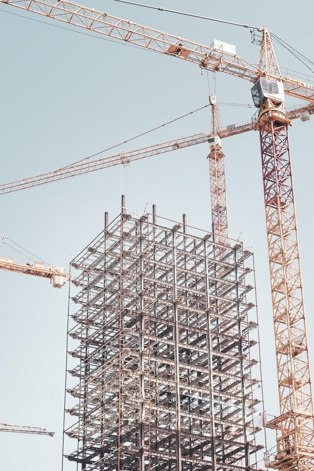 Een gebouw staat in steigers met twee heiskranen ernaast.