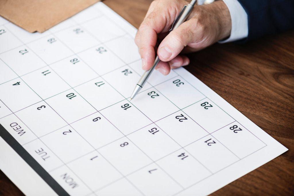 Een hand met een pen wijst een datum aan op een kalender